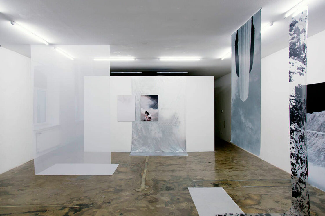 Raumansicht mit hängenden Tüchern, Folien, Fotos und am Boden liegenden Flächen