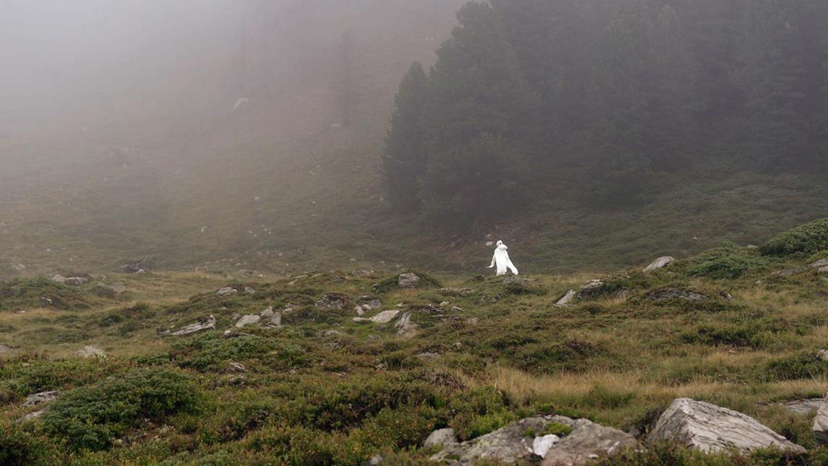 Weißgekleidete Figur im Nebel auf einer Berghöhe