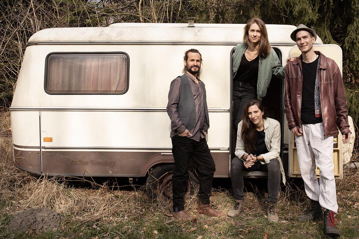 4 Personen vor einem alten Wohnwagen